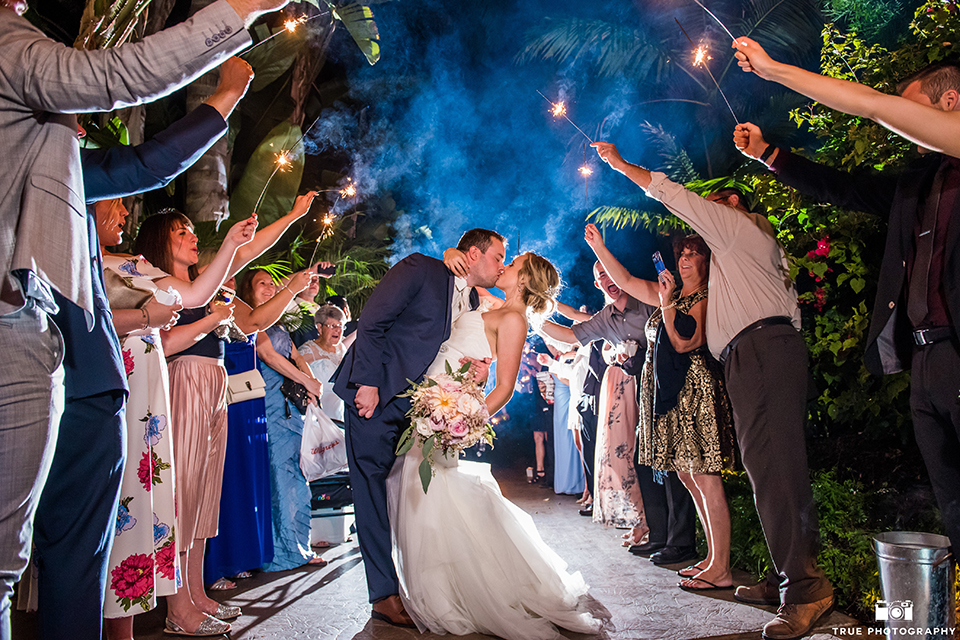 San diego outdoor wedding at the grand tradition estate bride form fitting mermaid style strapless gown with a crystal belt and groom navy blue notch lapel suit with a matching vest and white dress shirt with a long white tie and white floral boutonniere kissing during sparkler exit