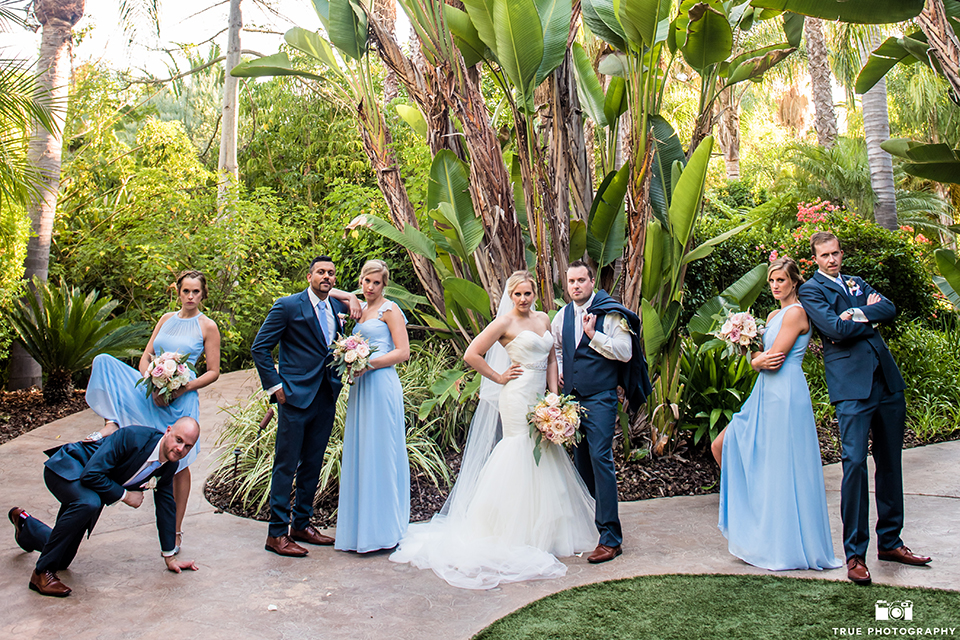 San diego outdoor wedding at the grand tradition estate bride form fitting mermaid style strapless gown with a crystal belt and groom navy blue notch lapel suit with a matching vest and white dress shirt with a long white tie and white floral boutonniere hugging with wedding party bridesmaids long light blue dresses with groomsmen navy suits with long light blue ties