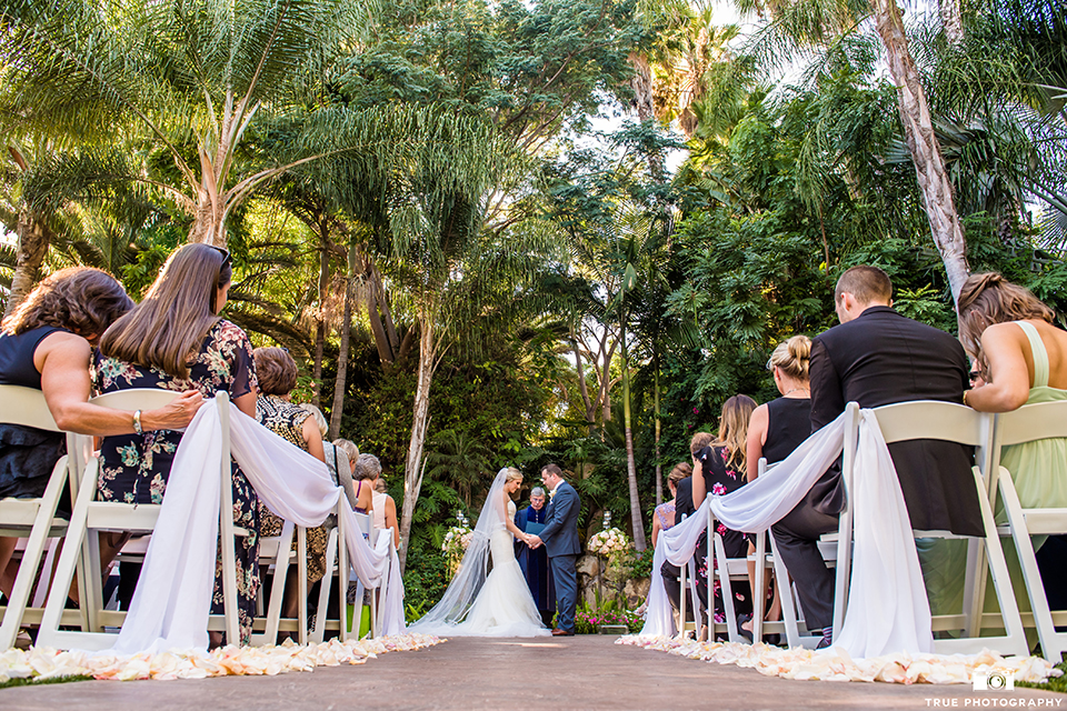 San diego outdoor wedding at the grand tradition estate bride form fitting mermaid style strapless gown with a crystal belt and groom navy blue notch lapel suit with a matching vest and white dress shirt with a long white tie and white floral boutonniere holding hands during ceremony