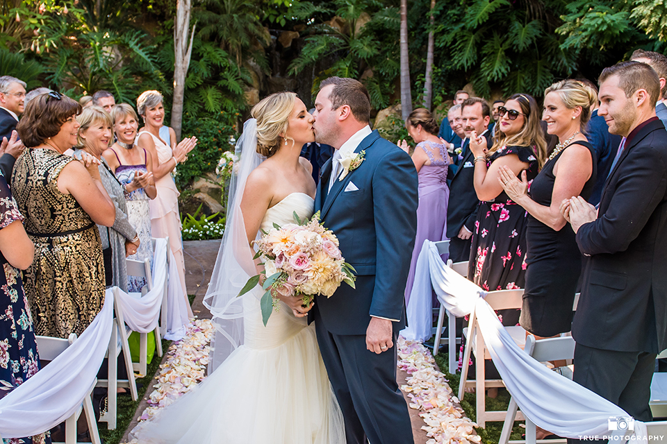 San diego outdoor wedding at the grand tradition estate bride form fitting mermaid style strapless gown with a crystal belt and groom navy blue notch lapel suit with a matching vest and white dress shirt with a long white tie and white floral boutonniere kissing after ceremony in aisle bride holding white and green floral bridal bouquet