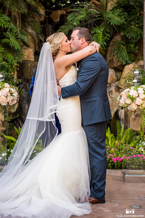 San diego outdoor wedding at the grand tradition estate bride form fitting mermaid style strapless gown with a crystal belt and groom navy blue notch lapel suit with a matching vest and white dress shirt with a long white tie and white floral boutonniere hugging and kissing during ceremony