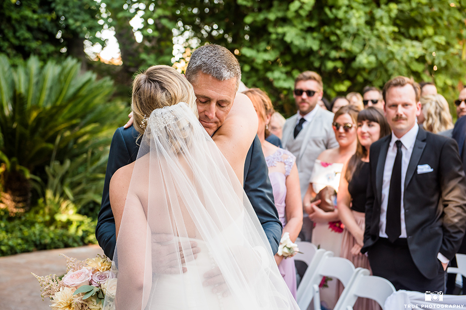 San diego outdoor wedding at the grand tradition estate bride form fitting mermaid style strapless gown with a crystal belt holding white and green floral bridal bouquet walking down the aisle with dad hugging