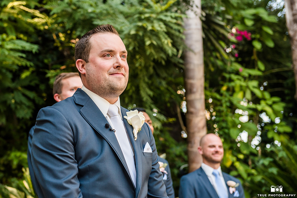 San diego outdoor wedding at the grand tradition estate groom navy blue notch lapel suit with a matching vest and white dress shirt with a long white tie and white floral boutonniere watching bride walk down the aisle during ceremony