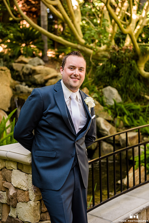 San diego outdoor wedding at the grand tradition estate groom navy blue notch lapel suit with a matching vest and white dress shirt with a long white tie and white floral boutonniere