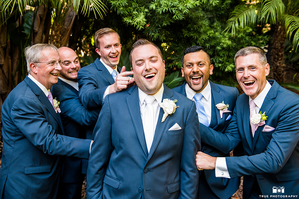 San diego outdoor wedding at the grand tradition estate groom navy blue notch lapel suit with a matching vest and white dress shirt with a long white tie and white floral boutonniere with groomsmen navy suits with long light blue striped ties