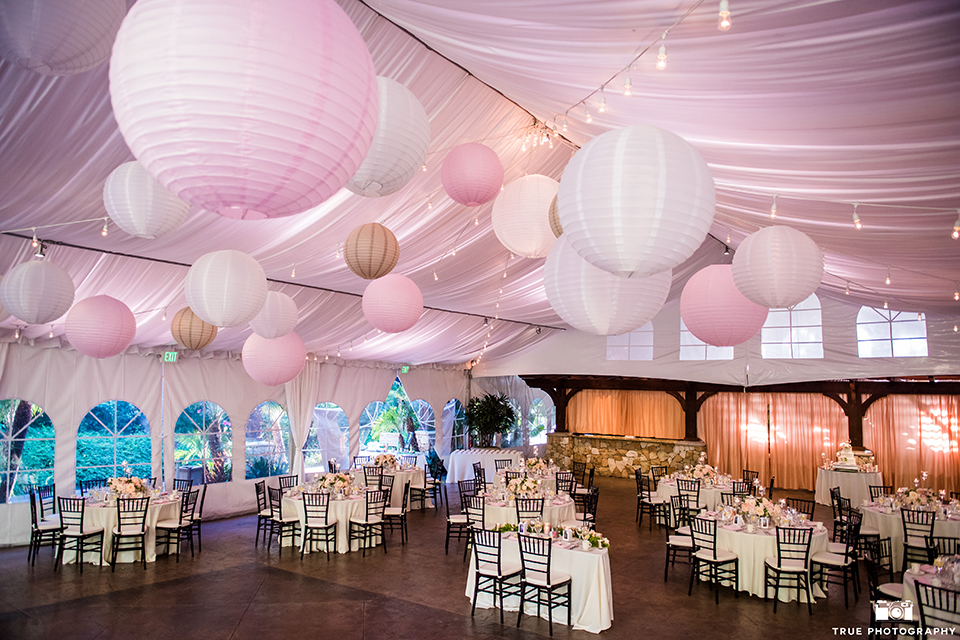 San diego outdoor wedding at the grand estate tradition reception set up with tables and white table linen with dark chairs and white place settings with pink napkin linen and hanging pink and white lantern decor with white and pink flower centerpiece decor