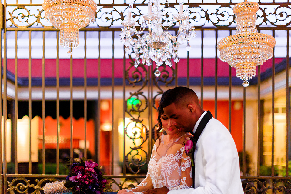 Orange county wedding shoot at jazz kitchen downtown disney bride form fitting lace gown with long illusion sleeves and sweetheart neckline with an open back design and groom white with black shawl lapel tuxedo with white dress shirt and black pants with a black bow tie and purple floral boutonniere standing and hugging