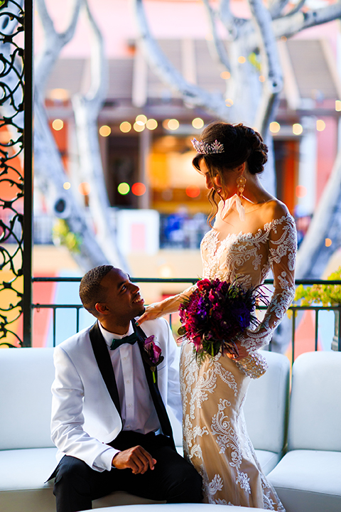 Orange county wedding shoot at jazz kitchen downtown disney bride form fitting lace gown with long illusion sleeves and sweetheart neckline with an open back design and groom white with black shawl lapel tuxedo with white dress shirt and black pants with a black bow tie and purple floral boutonniere sitting with bride standing holding purple floral bridal bouquet