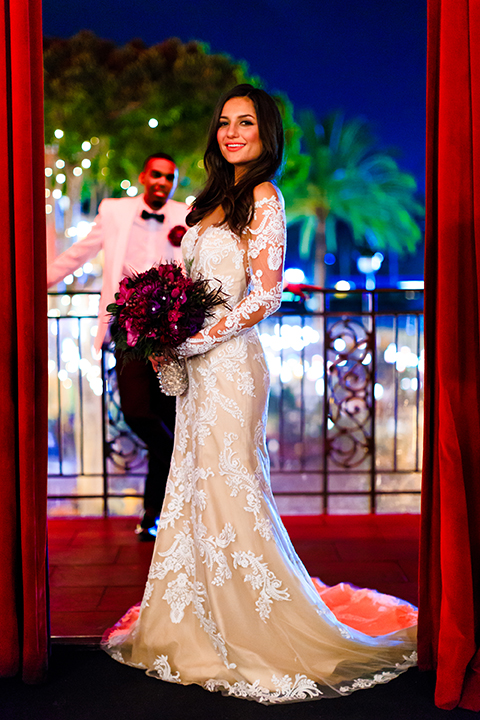Orange county wedding shoot at jazz kitchen downtown disney bride form fitting lace gown with long illusion sleeves and sweetheart neckline with an open back design and groom white dinner jacket with a white dress shirt and black pants with a green bow tie standing and bride holding purple floral bridal bouquet