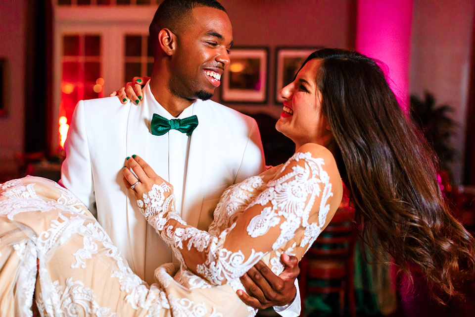Orange county wedding shoot at jazz kitchen downtown disney bride form fitting lace gown with long illusion sleeves and sweetheart neckline with an open back design and groom white dinner jacket with a white dress shirt and black pants with a green bow tie holding and carrying bride