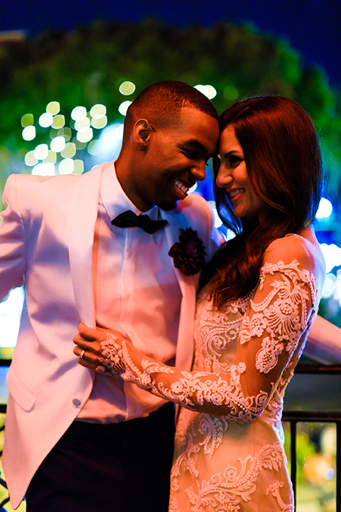 Orange county wedding shoot at jazz kitchen downtown disney bride form fitting lace gown with long illusion sleeves and sweetheart neckline with an open back design and groom white dinner jacket with a white dress shirt and black pants with a green bow tie standing and hugging