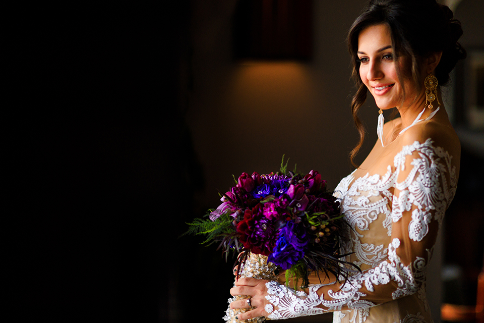 Orange county wedding shoot at jazz kitchen downtown disney bride form fitting lace gown with long illusion sleeves and sweetheart neckline with an open back design holding purple floral bridal bouquet