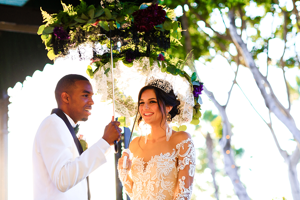 Orange county wedding shoot at jazz kitchen downtown disney bride form fitting lace gown with long illusion sleeves and sweetheart neckline with an open back design and groom white with black shawl lapel tuxedo with white dress shirt and black pants with a black bow tie and purple floral boutonniere holding lace umbrellas with flower decor