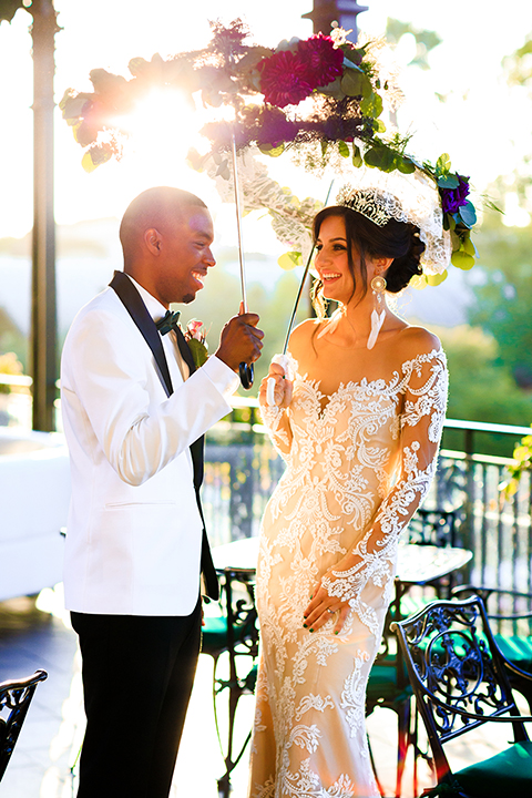 Orange county wedding shoot at jazz kitchen downtown disney bride form fitting lace gown with long illusion sleeves and sweetheart neckline with an open back design and groom white with black shawl lapel tuxedo with white dress shirt and black pants with a black bow tie and purple floral boutonniere standing and holding lace umbrellas with flower decor