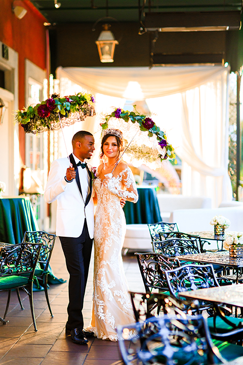 Orange county wedding shoot at jazz kitchen downtown disney bride form fitting lace gown with long illusion sleeves and sweetheart neckline with an open back design and groom white with black shawl lapel tuxedo with white dress shirt and black pants with a black bow tie and purple floral boutonniere standing and hugging holding lace umbrellas with flower decor