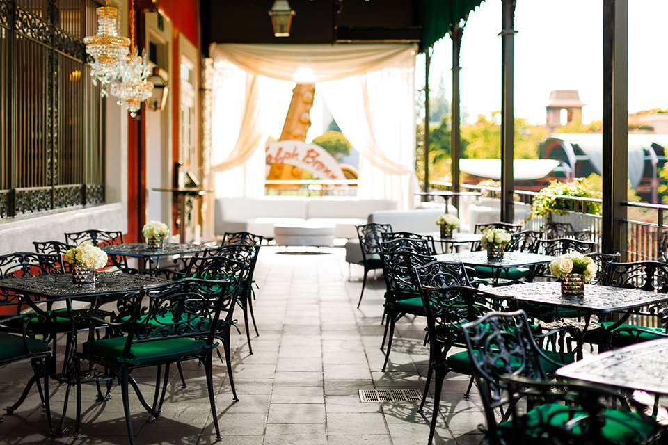 Orange county wedding shoot at jazz kitchen downtown disney ceremony set up outside patio with white chiffon draping on alter with black and green chairs and tables with flower decor wedding photo idea for ceremony set up