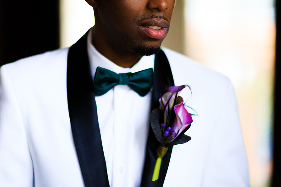Orange county wedding shoot at jazz kitchen downtown disney groom white with black shawl lapel tuxedo with a white dress shirt and a black bow tie and black pants with a purple floral boutonniere close up