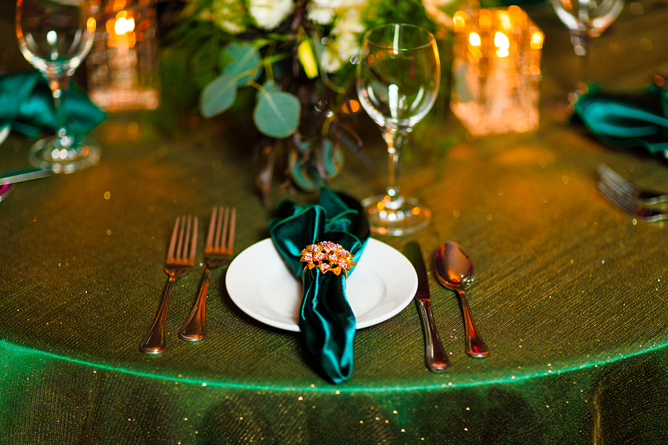 Orange county wedding shoot at jazz kitchen reception table set up with dark green table linen and white place settings with matching green napkin linens and white and green and purple flower centerpiece decor with glassware and silverware and chairs
