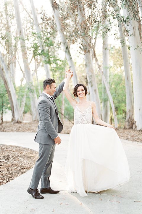 Southern california outdoor into the woods wedding shoot bride a line gown with a detailed beaded bodice with thin straps and a plunging neckline with groom grey notch lapel suit with a matching vest and white dress shirt with a long charcoal grey tie dancing and spinning