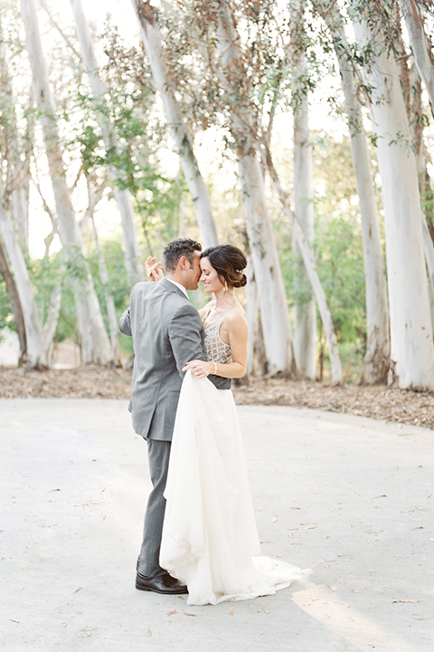 Southern california outdoor into the woods wedding shoot bride a line gown with a detailed beaded bodice with thin straps and a plunging neckline with groom grey notch lapel suit with a matching vest and white dress shirt with a long charcoal grey tie dancing and holding hands