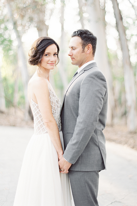 Southern california outdoor into the woods wedding shoot bride a line gown with a detailed beaded bodice with thin straps and a plunging neckline with groom grey notch lapel suit with a matching vest and white dress shirt with a long charcoal grey tie standing and holding hands