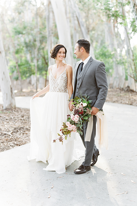 Southern california outdoor into the woods wedding shoot bride a line gown with a detailed beaded bodice with thin straps and a plunging neckline with groom grey notch lapel suit with a matching vest and white dress shirt with a long charcoal grey tie walking and holding hands groom holding white and dark red floral bridal bouquet