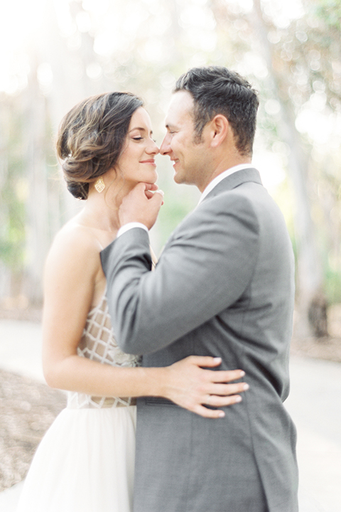 Southern california outdoor into the woods wedding shoot bride a line gown with a detailed beaded bodice with thin straps and a plunging neckline with groom grey notch lapel suit with a matching vest and white dress shirt with a long charcoal grey tie hugging and kissing