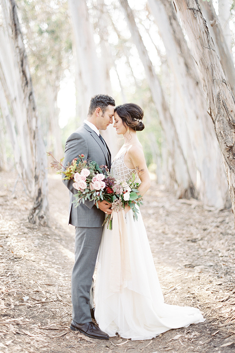 Southern california outdoor into the woods wedding shoot bride a line gown with a detailed beaded bodice with thin straps and a plunging neckline with groom grey notch lapel suit with a matching vest and white dress shirt with a long charcoal grey tie hugging and bride holding white and dark red floral bridal bouquet