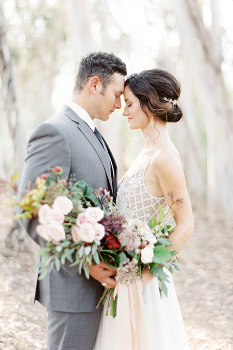 Southern california outdoor into the woods wedding shoot bride a line gown with a detailed beaded bodice with thin straps and a plunging neckline with groom grey notch lapel suit with a matching vest and white dress shirt with a long charcoal grey tie hugging close up bride holding white and dark red floral bridal bouquet