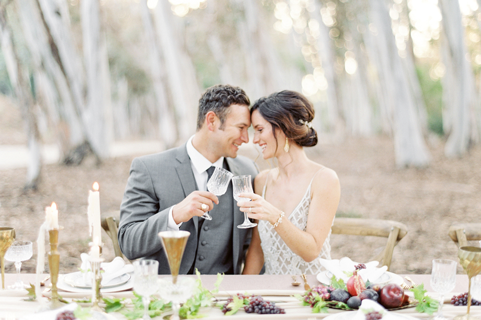 Southern california outdoor into the woods wedding shoot bride a line gown with a detailed beaded bodice with thin straps and a plunging neckline with groom grey notch lapel suit with a matching vest and white dress shirt with a long charcoal grey tie sitting at table holding drinks