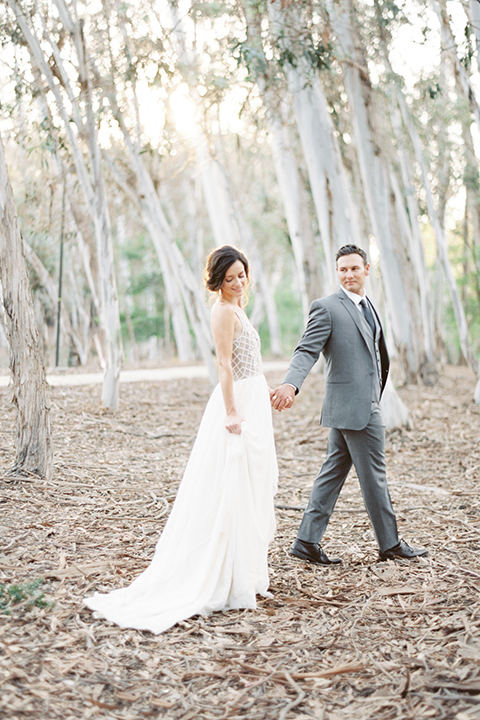 Southern california outdoor into the woods wedding shoot bride a line gown with a detailed beaded bodice with thin straps and a plunging neckline with groom grey notch lapel suit with a matching vest and white dress shirt with a long charcoal grey tie walking and holding hands