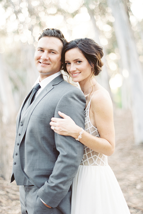 Southern california outdoor into the woods wedding shoot bride a line gown with a detailed beaded bodice with thin straps and a plunging neckline with groom grey notch lapel suit with a matching vest and white dress shirt with a long charcoal grey tie hugging close up