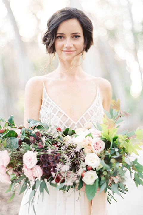 Southern california outdoor into the woods wedding shoot bride a line gown with a detailed beaded bodice with thin straps and a plunging neckline holding white and dark red floral bridal bouquet close up