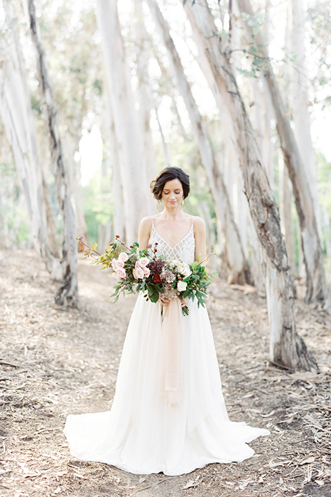 Southern california outdoor into the woods wedding shoot bride a line gown with a detailed beaded bodice with thin straps and a plunging neckline holding white and dark red floral bridal bouquet
