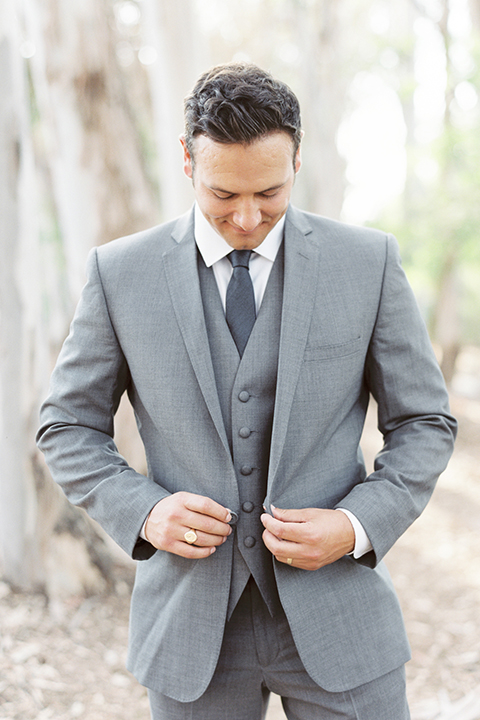 Southern california outdoor into the woods wedding shoot groom grey notch lapel suit with a matching vest and white dress shirt with a long charcoal grey tie buttoning jacket close up