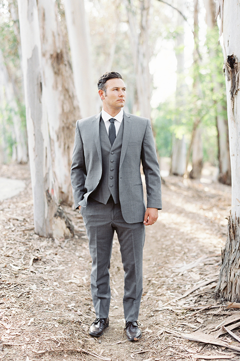 Southern california outdoor into the woods wedding shoot groom grey notch lapel suit with a matching vest and white dress shirt with a long charcoal grey tie standing with hands in pockets
