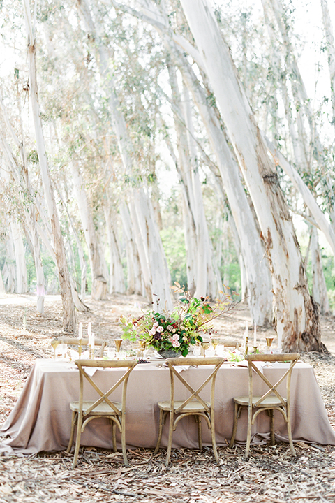 Southern california outdoor into the woods wedding shoot table set up light cream colored linen with white place settings and grapes on white linen napkins with light brown wooden chairs and white candles with gold stands and whit and green and dark red flower centerpiece decor