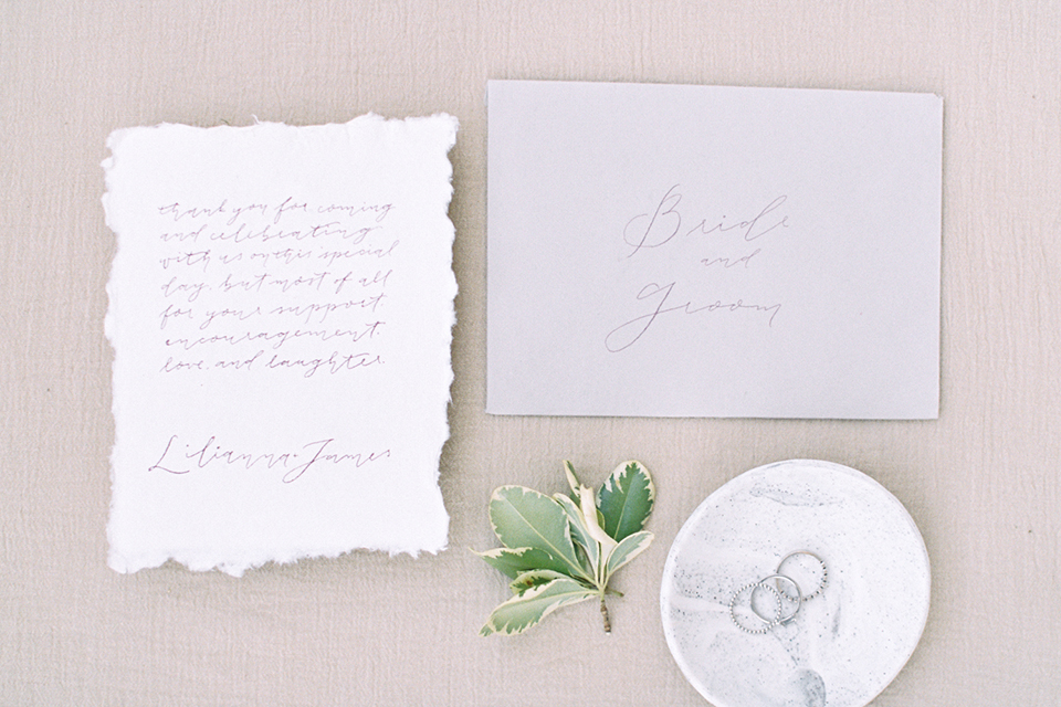 Southern california outdoor into the woods wedding shoot wedding invitations white invitations with callligraphy writing and light grey envelopes with green flower decor and white dish with wedding rings on light cream linen background wedding photo idea for invitations